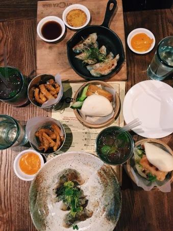 meal at gyoza bar of dumplings, sweet potato fries, bro buns and sauces/dips