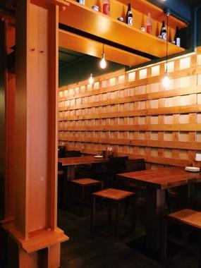 gyoza bar restaurant space. wooden tables and open brick walls